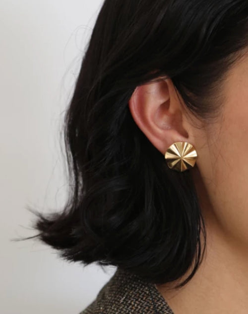 Image of model wearing the Cala studs in gold by Lisbeth.