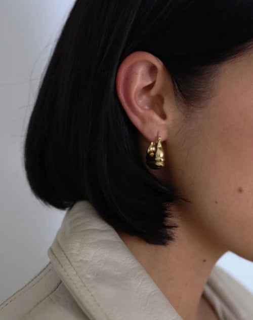 Image of a model wearing the Emily earrings in gold by Lisbeth.