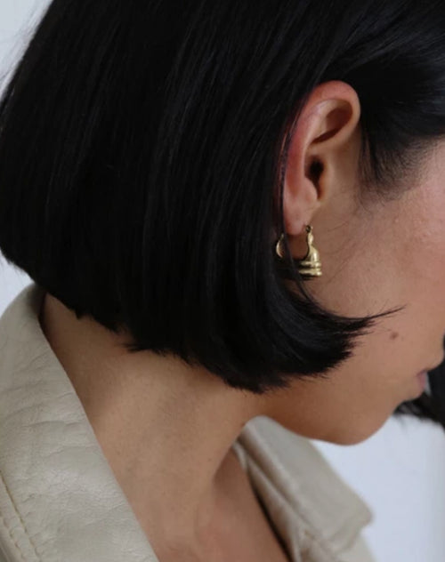 Side photo of a model wearing the Emily earrings in gold by Lisbeth.