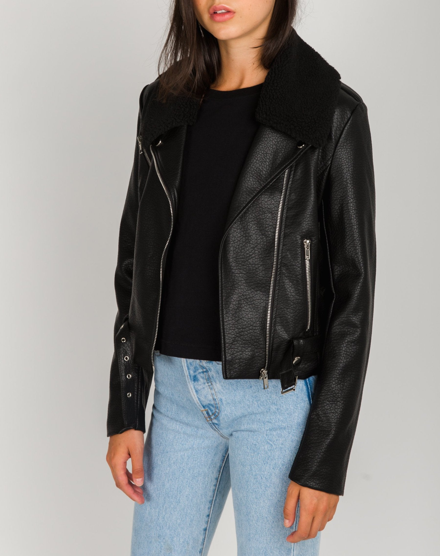 Left side photo of the Florence vegan leather moto jacket with shearling collar in black by Brunette the Label.