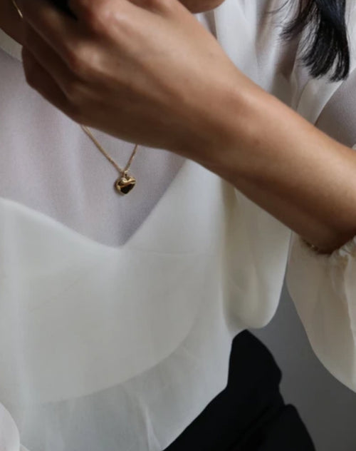 Image of a model wearing the Heart Locket box chain in gold by Lisbeth.