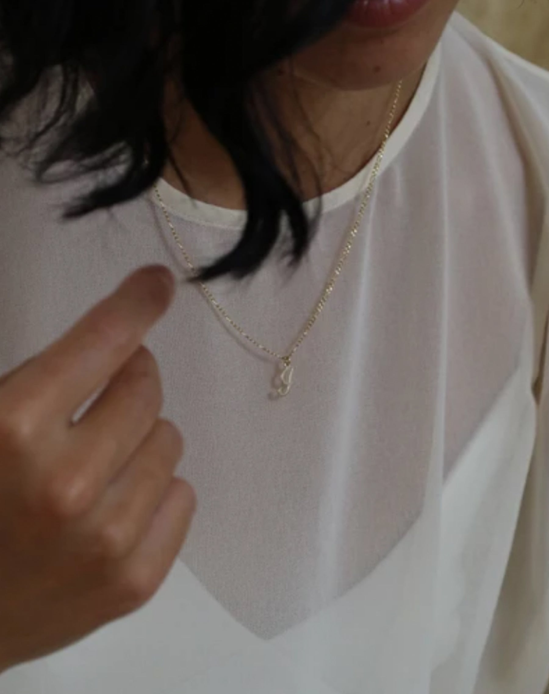 Photo of model wearing the initial necklace in gold figaro chain by Lisbeth.