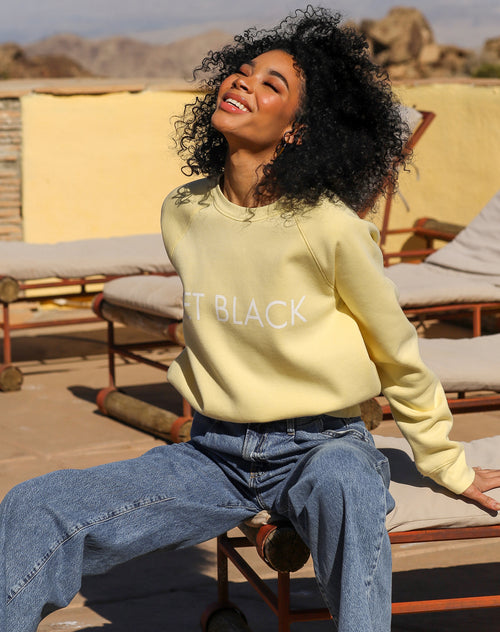 This is a campaign photo of the Jet Black Lemon Classic Crew neck Sweatshirt by Brunette the Label