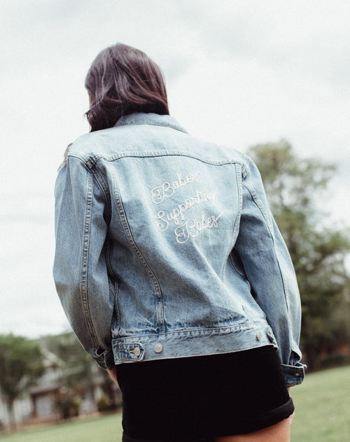 Photo of the Babes Supporting Babes embroidered on the Lindsay denim jacket in light wash by Brunette the Label.