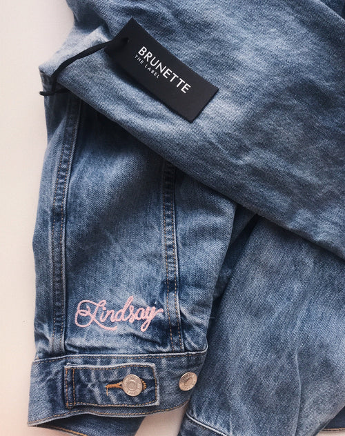 Photo of an example of customized embroidered name on the Lindsay denim jacket in light wash by Brunette the Label.