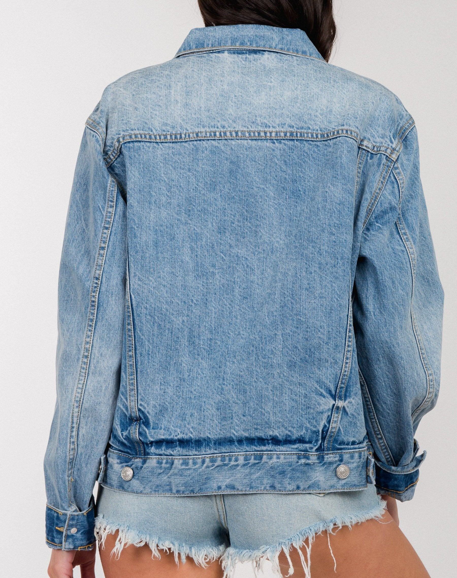 Photo of the back of the Lindsay denim jacket in light wash by Brunette the Label.
