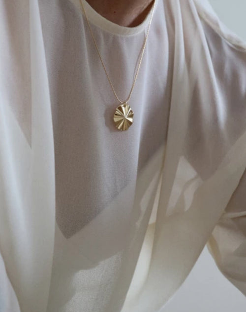Image of a model wearing the Mila necklace in gold by Lisbeth.