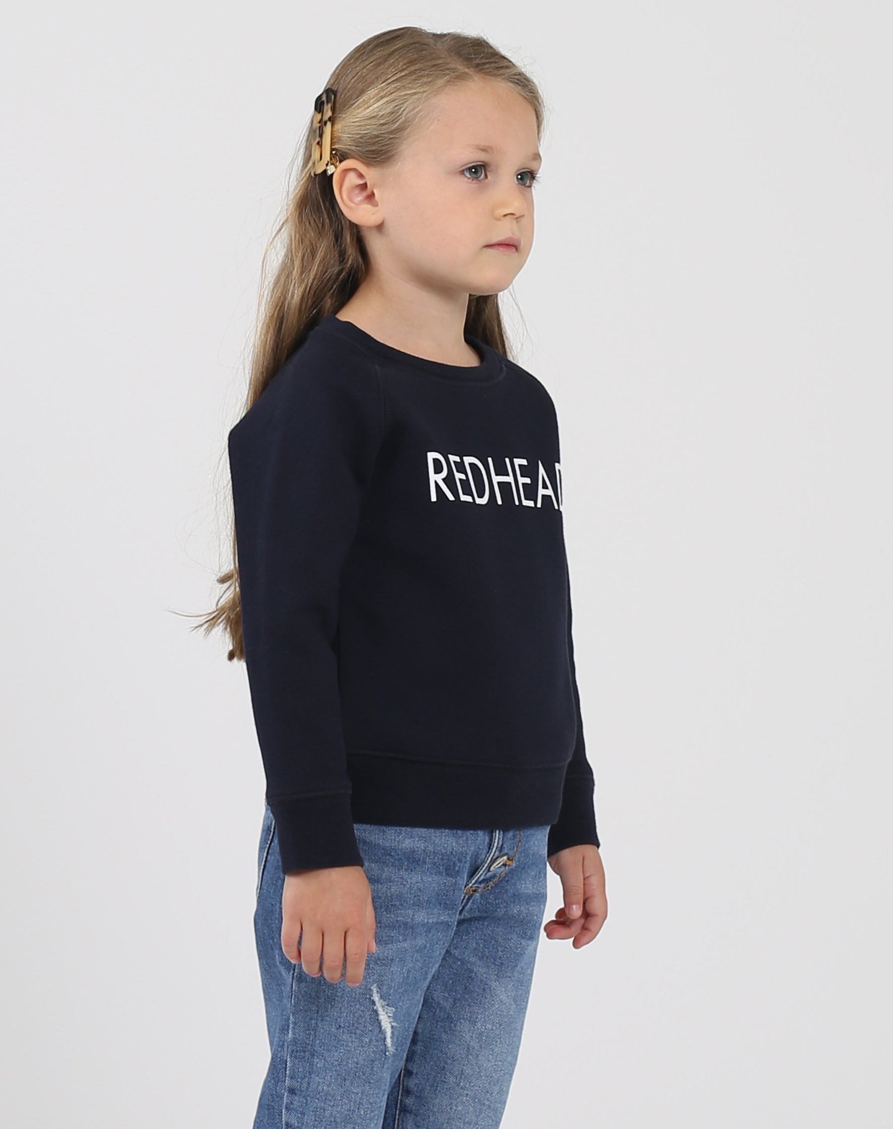 Photo of the side of the Redhead Little Babes classic crew neck sweatshirt in navy by Brunette the Label.