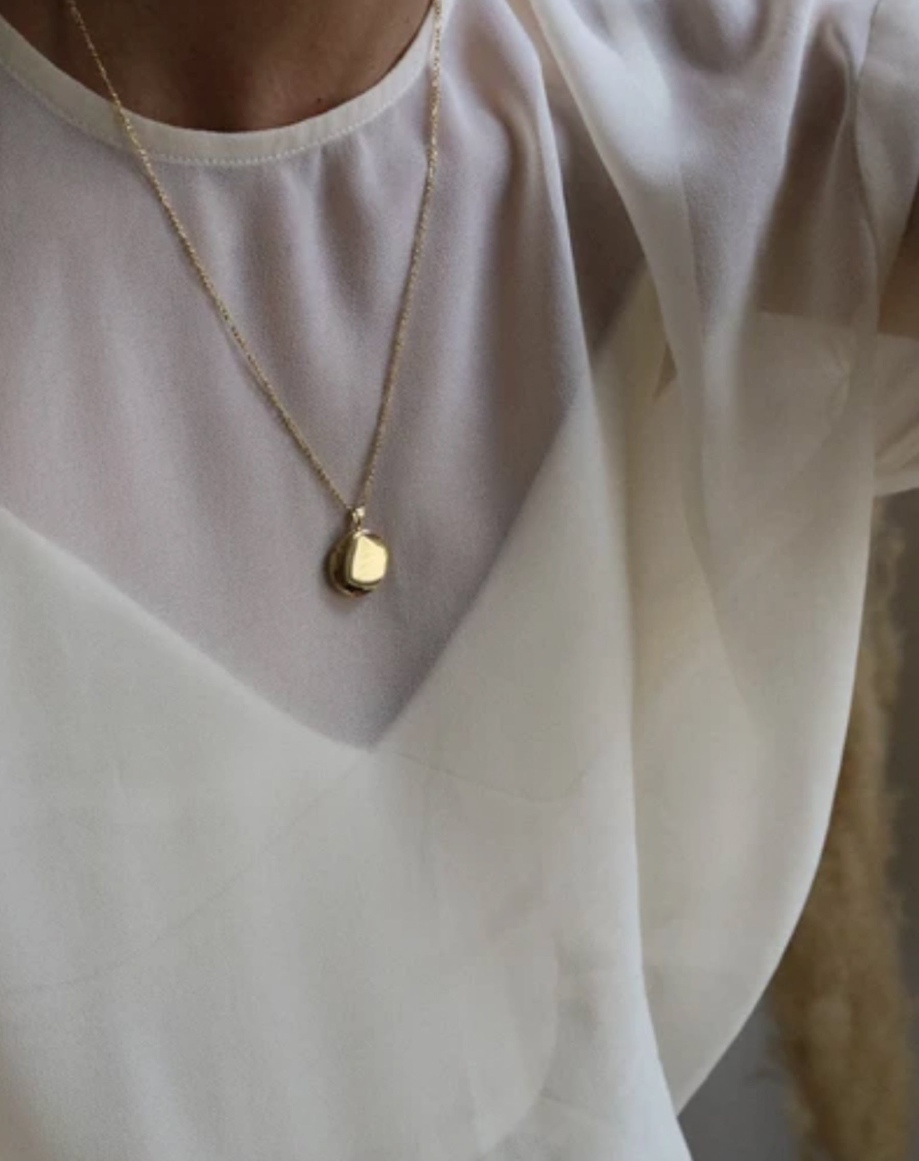 Image of a model wearing the Round Locket in gold by Lisbeth.