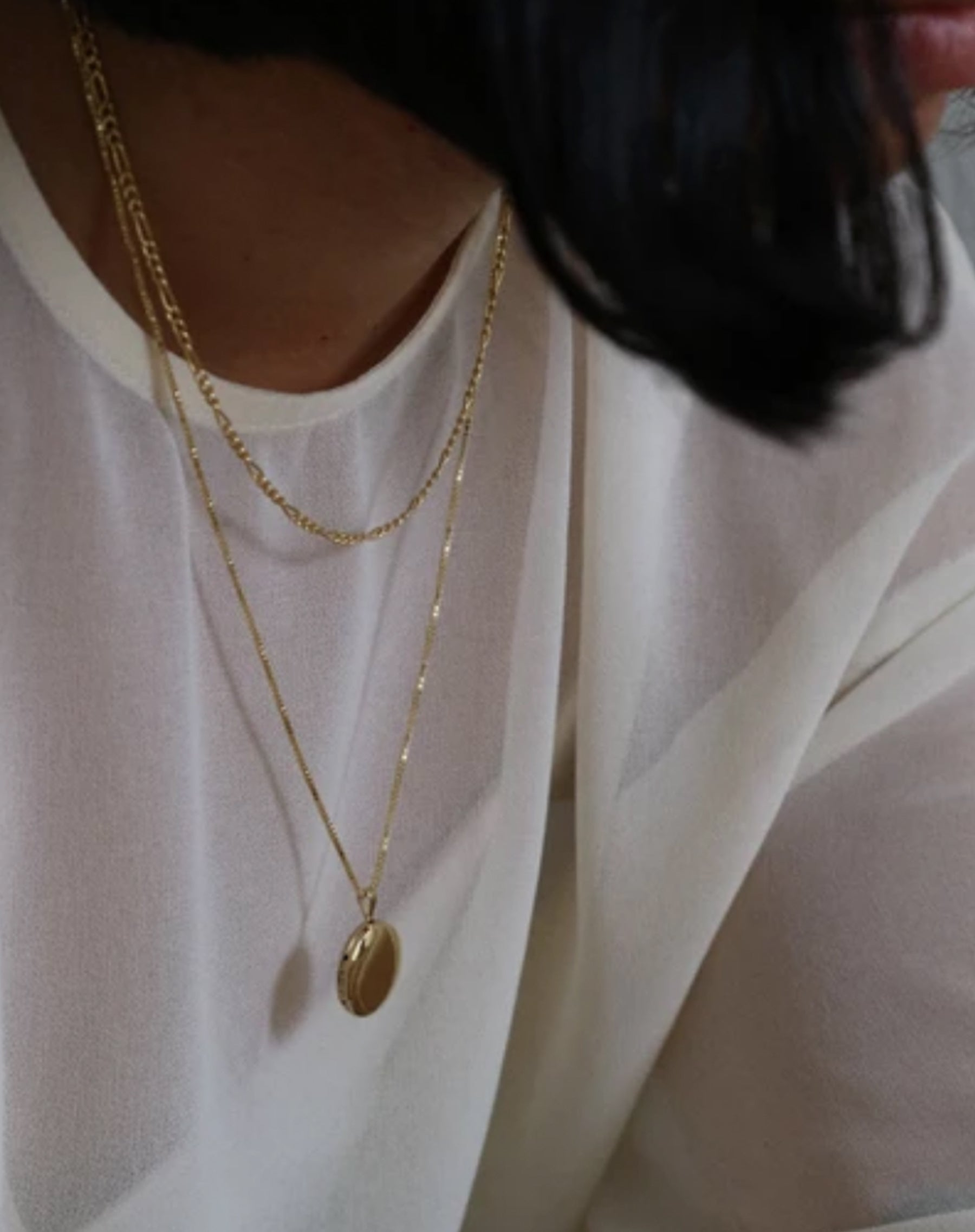 Second image of a model wearing the Round Locket in gold by Lisbeth.