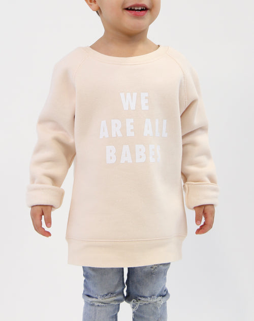 Photo 2 of child wearing the We Are All Babes classic crew neck sweatshirt in peach crush by Brunette the Label.