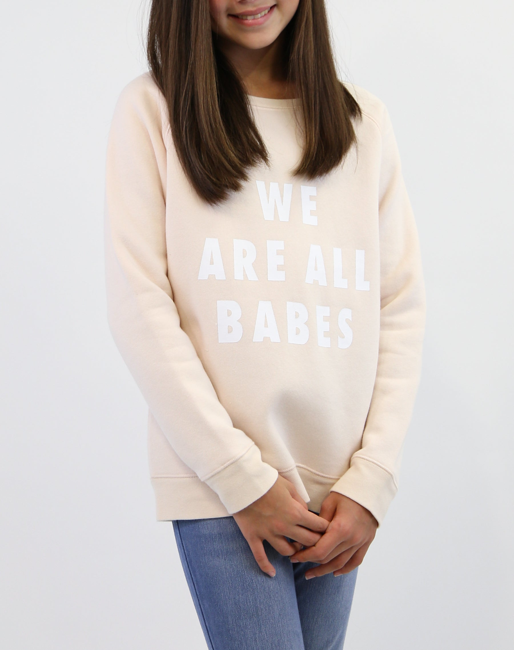 Photo of child wearing the We Are All Babes classic crew neck sweatshirt in peach crush by Brunette the Label.