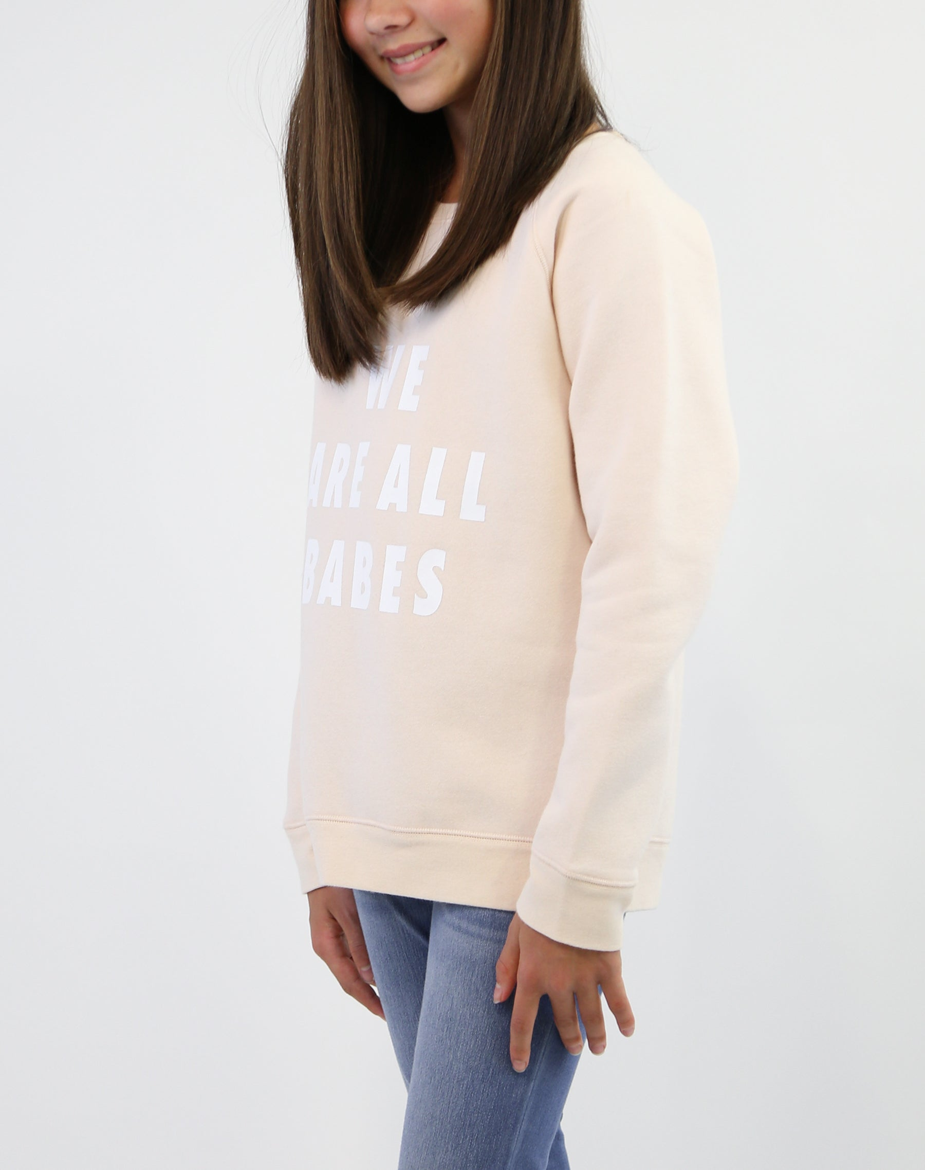 Photo 3 of child wearing the We Are All Babes classic crew neck sweatshirt in peach crush by Brunette the Label.
