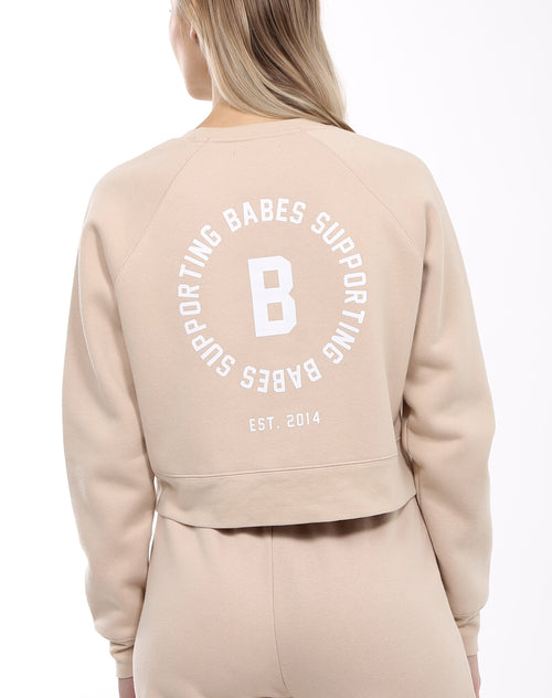 Photo of the back of the Babes Supporting Babes little sister crew neck sweatshirt in toasted almond by Brunette the Label.