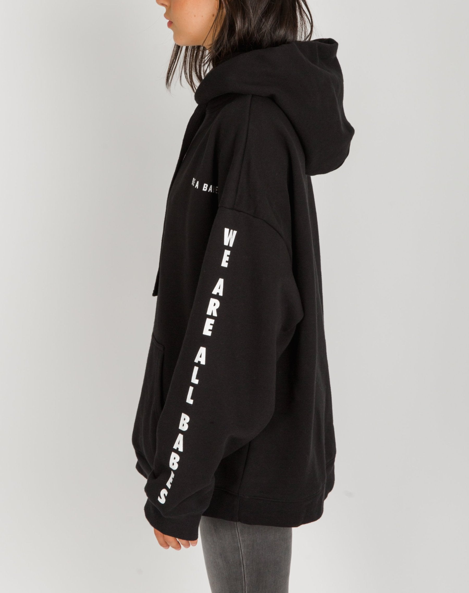 Side photo of the Be a Babe big sister hoodie in black by Brunette the Label.