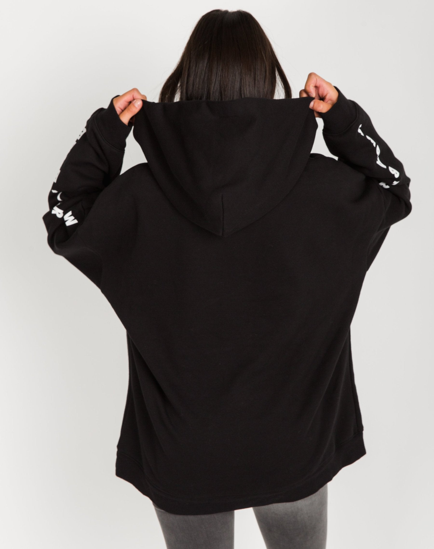Photo of the back of the Be a Babe big sister hoodie in black by Brunette the Label.