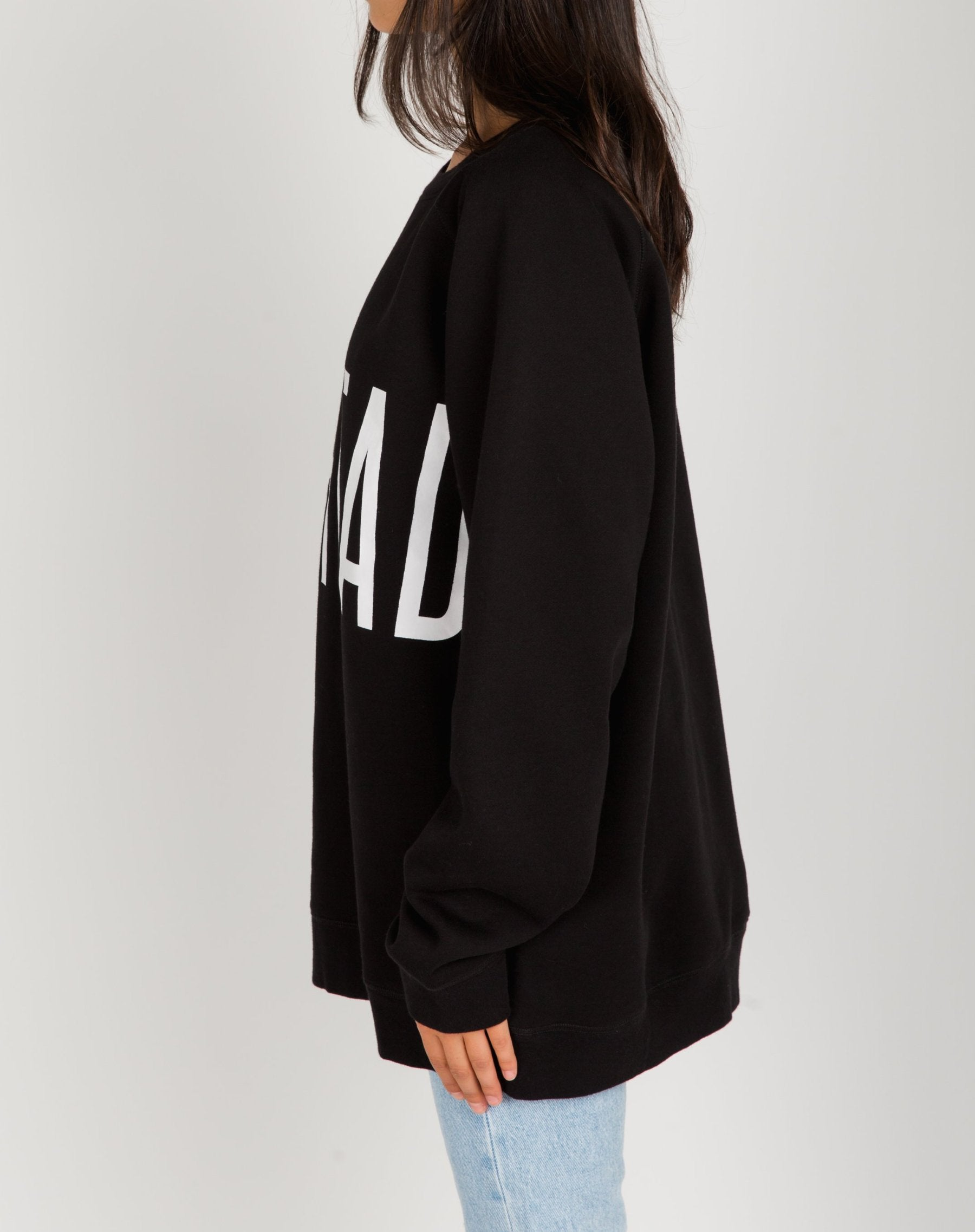 Photo of the side of the Redhead big sister crew neck sweatshirt in black by Brunette the Label.