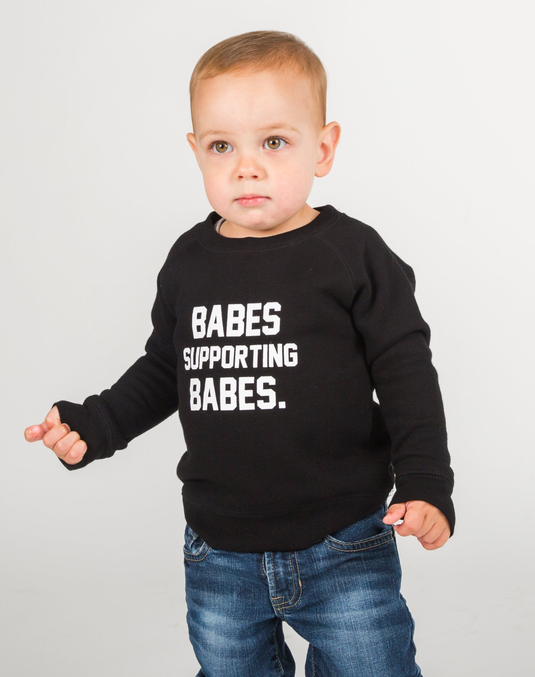 Photo of baby wearing the Babes Supporting Babes Little Babes classic crew neck sweatshirt in black by Brunette the Label.