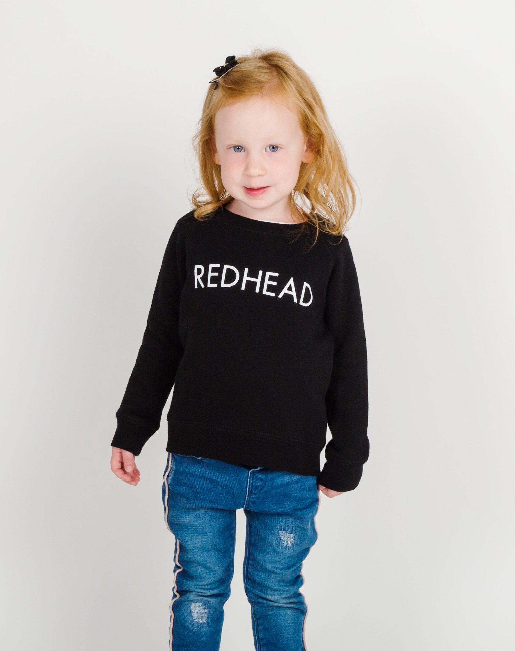 Photo of the Redhead Little Babes classic crew neck sweatshirt in black by Brunette the Label.