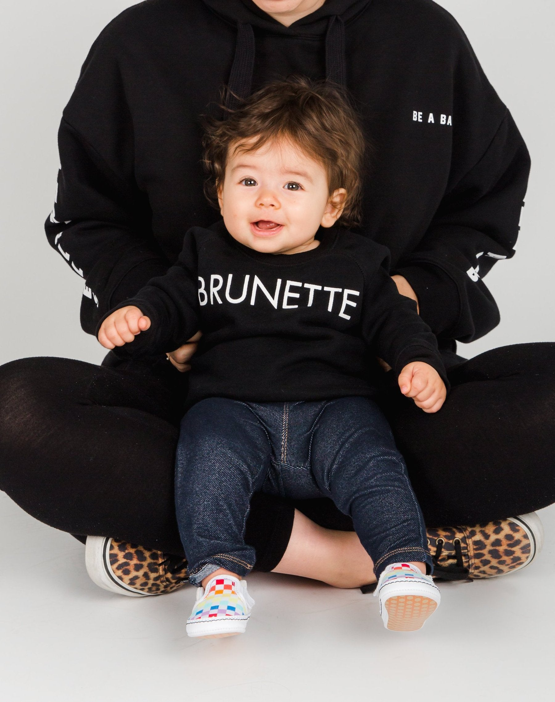 Photo of baby wearing the Brunette Little Babes classic crew neck sweatshirt in black by Brunette the Label.