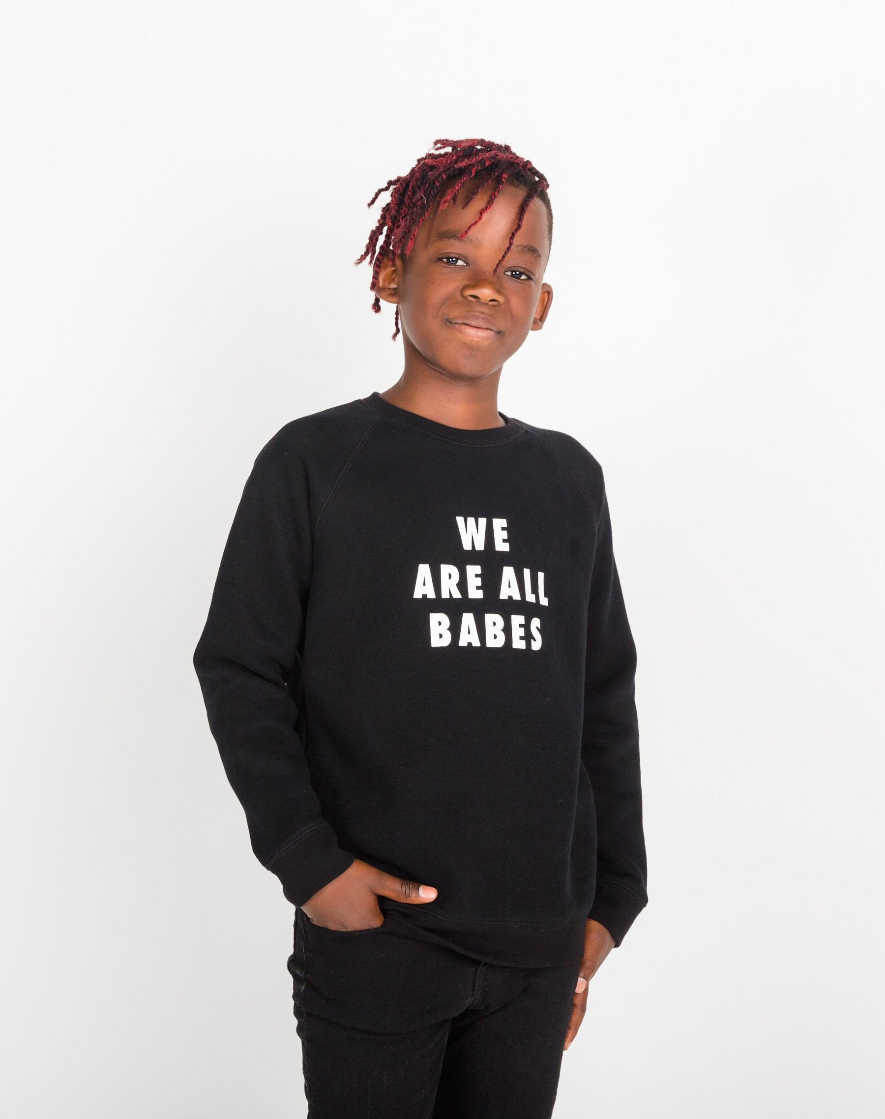 Photo of child wearing the We Are All Babes Little Babes classic crew neck sweatshirt in black by Brunette the Label.