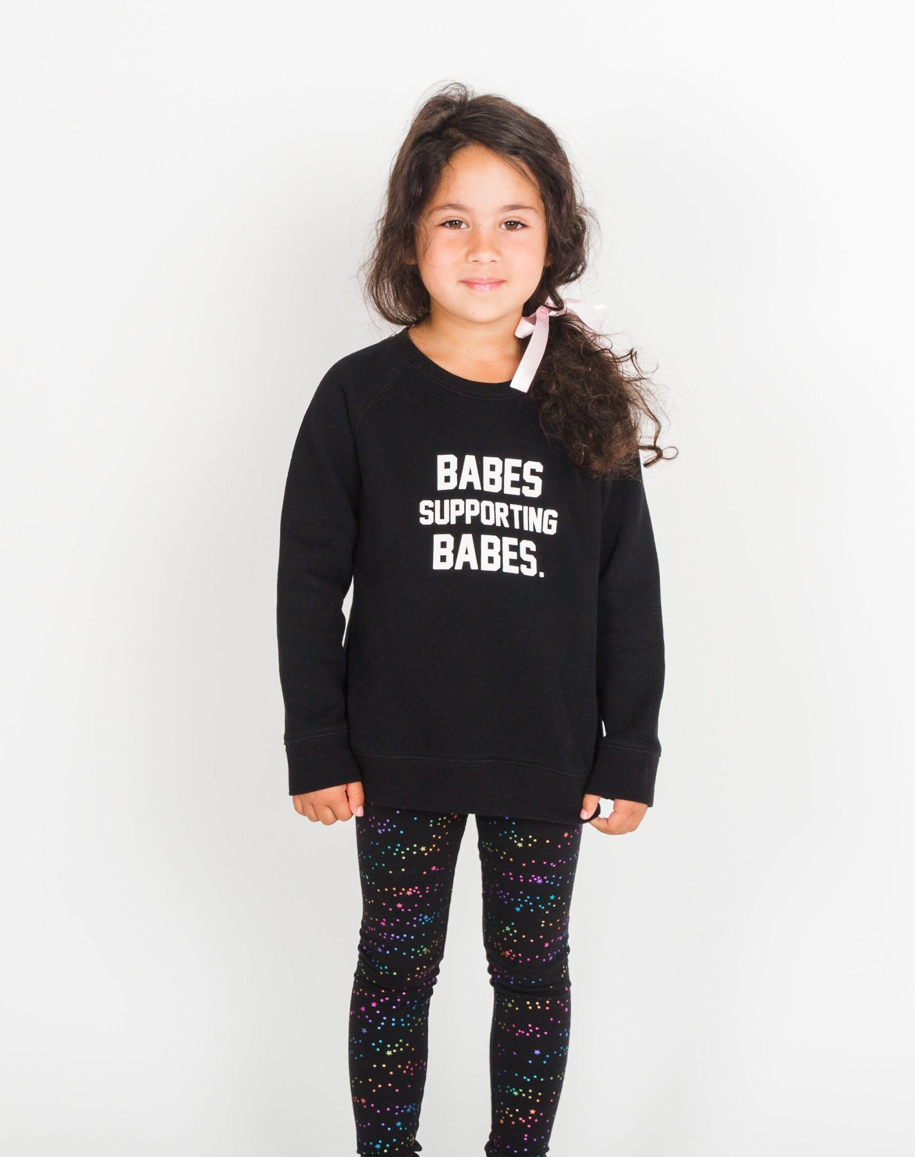 Photo of child wearing the Babes Supporting Babes Little Babes classic crew neck sweatshirt in black by Brunette the Label.