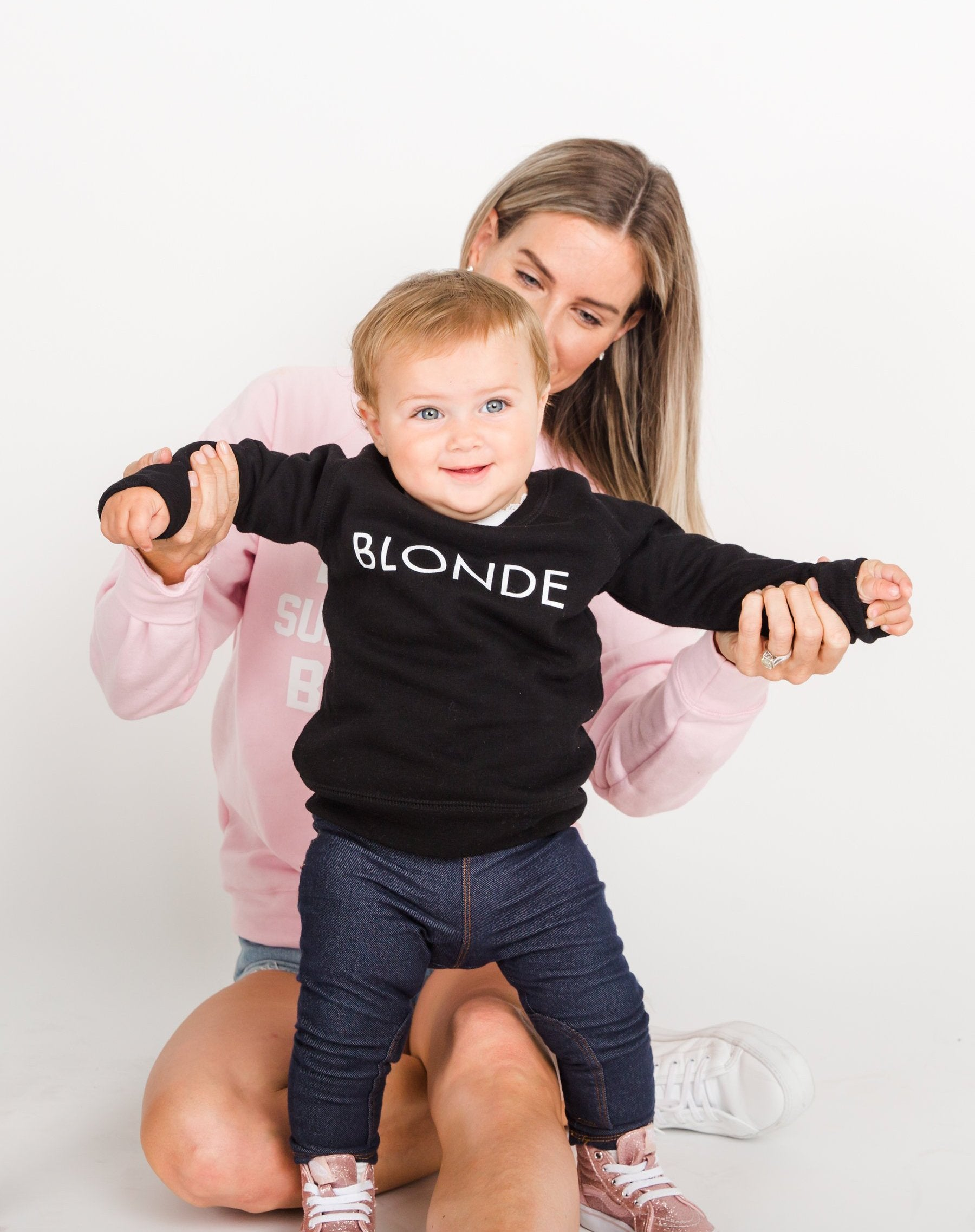 Photo of a baby wearing the Blonde Little Babes classic crew neck sweatshirt in black by Brunette the Label.