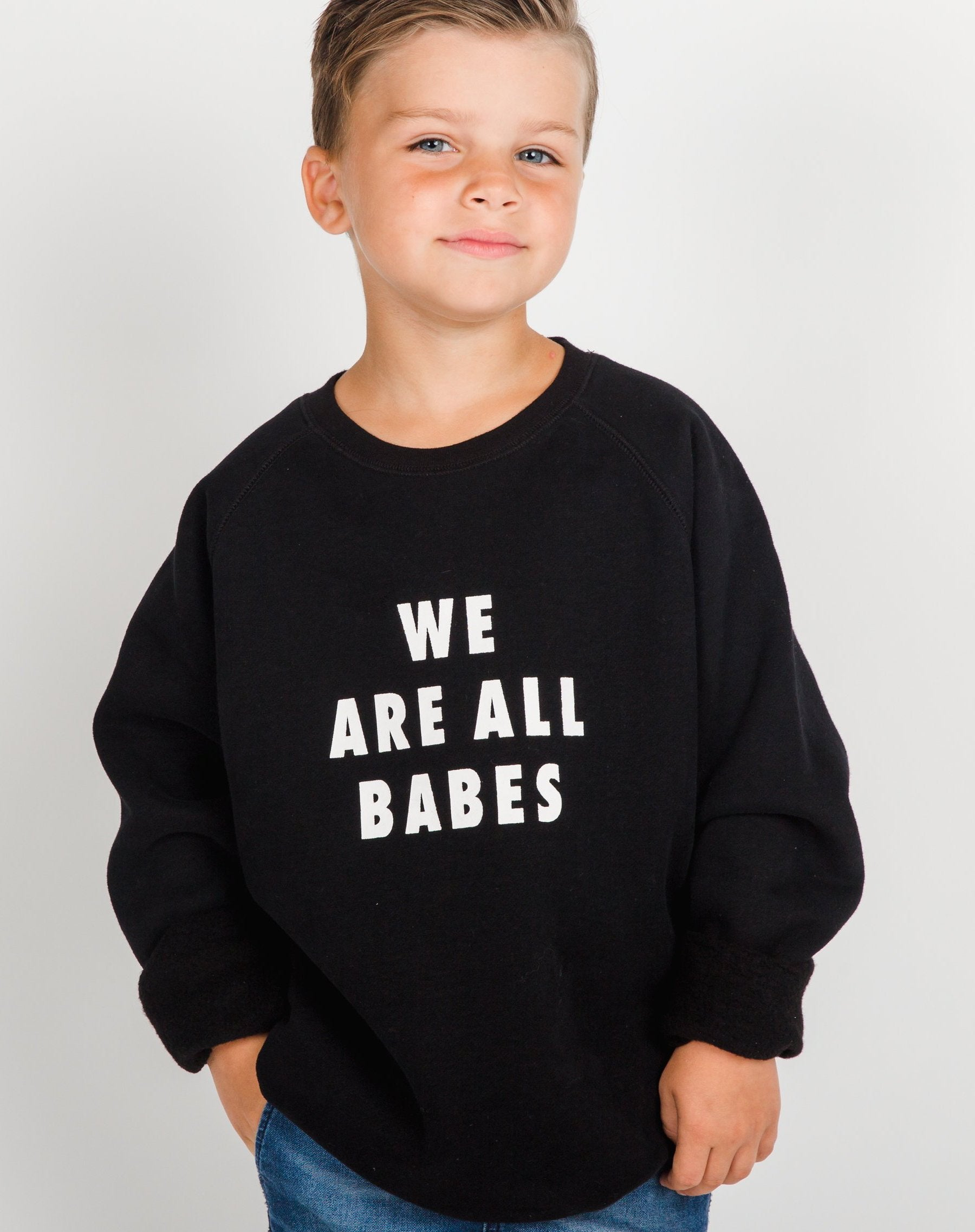 Photo of child 2 wearing the We Are All Babes Little Babes classic crew neck sweatshirt in black by Brunette the Label.