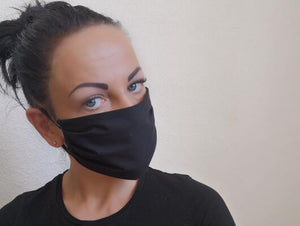 woman with cotton handmade reusable face mask face covering black with a filter pocket