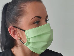 woman with cotton handmade reusable face mask face covering light green