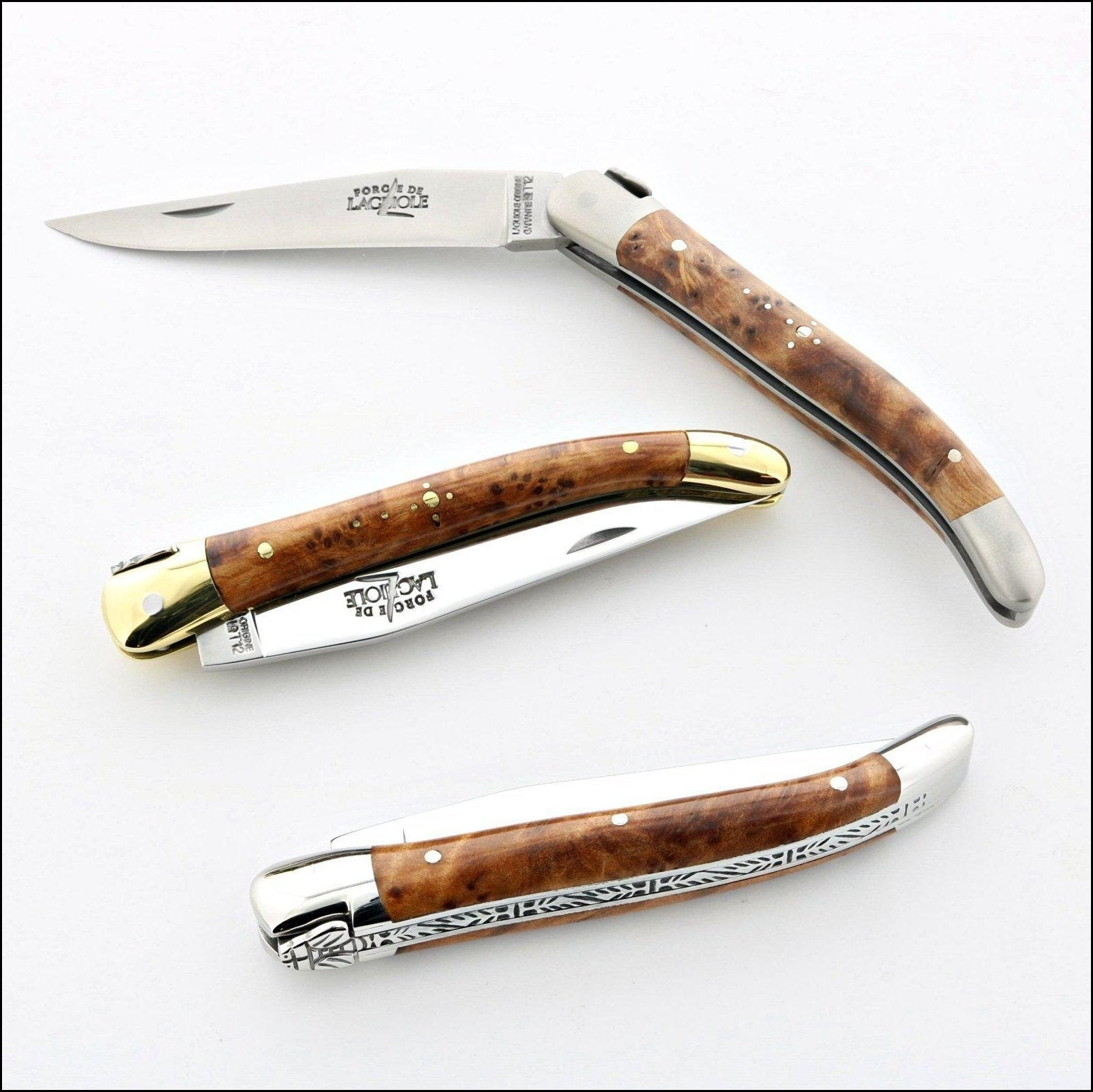 3 forge de laguiole knives of different finish. brass, shiny stainless  and brushed stainless. The wood handles are all thuya wood