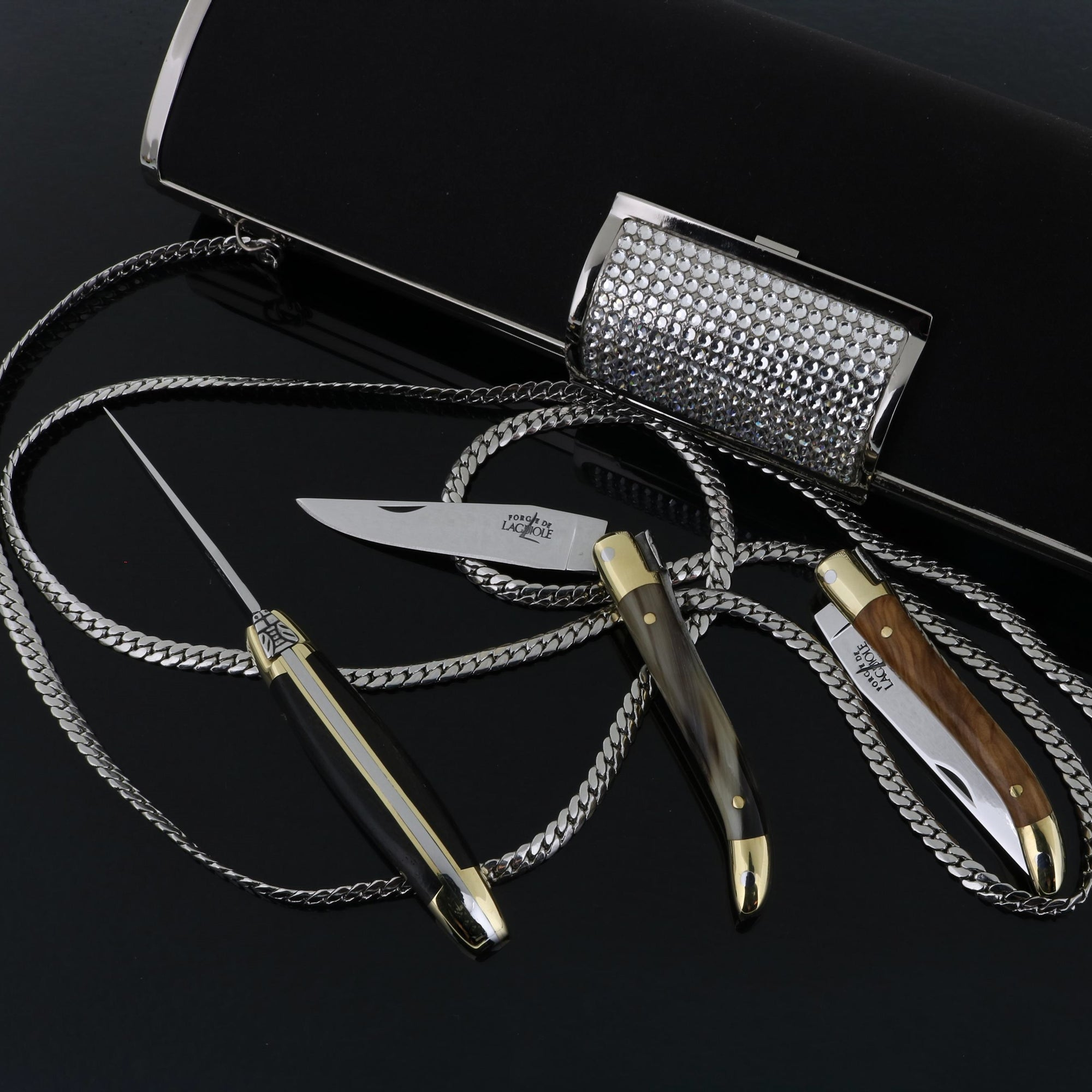 Black lady's purse with 3 small Laguiole pocket knives on a black background