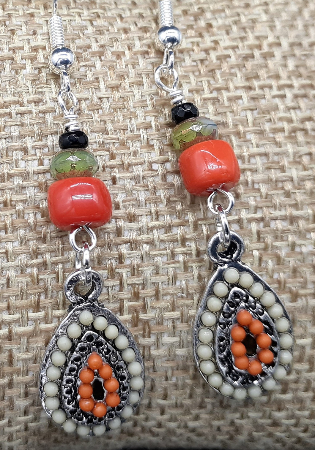Orange and ivory earrings covered in mini beads in an oval shape. Nice & Pretty Jewelry handcrafted in Canada
