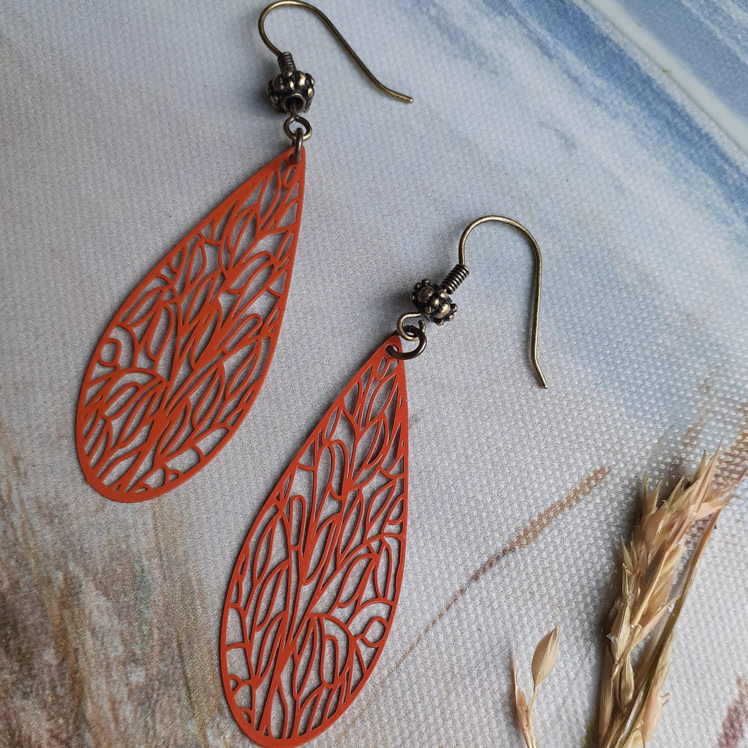 Laser cut design orange dragonfly wing earrings. Dragonfly wing earrings. Orange long oval earrings with patterns. Nice & Pretty Jewelry. Canada