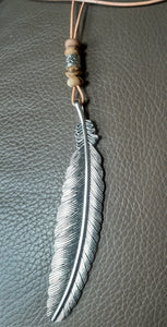 feather pendant on peach leather cord with bead accents. Nice & Pretty Jewelry
