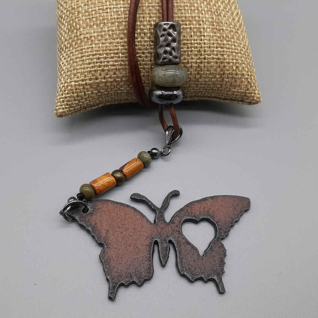 Butterfly pendant in rust finish. Butterfly pendant on leather necklace. Nice & Pretty Jewelry. Canada