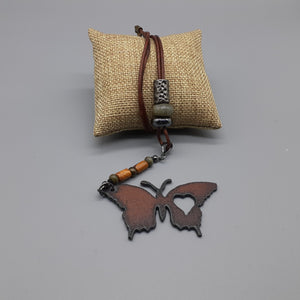 Butterfly pendant with rust finish on leather cord necklace. Nice & Pretty Jewelry. Canada
