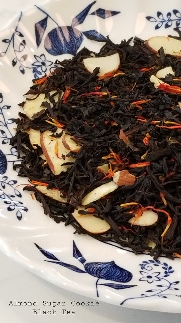 black tea leaves on a blue and white floral plate.  Has almond slices and red and yellow petals