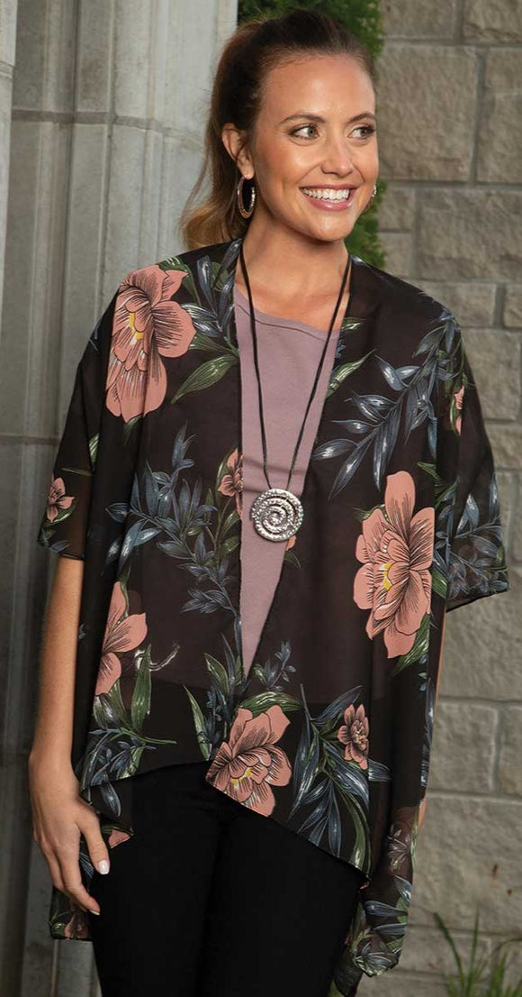 a model wearing our sheer black kimono with large pink and blue florals scattered all over with green leaves throughout.