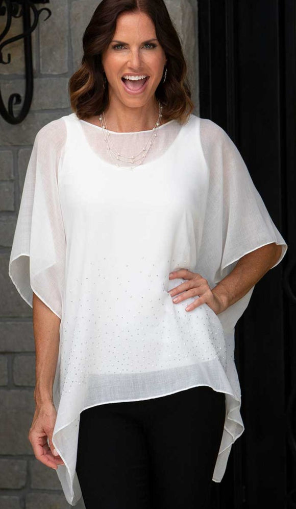 a brunette model wearing a lightweight white fabric tunic with pearls & sparkles scattered along the bottom half of the tunic.