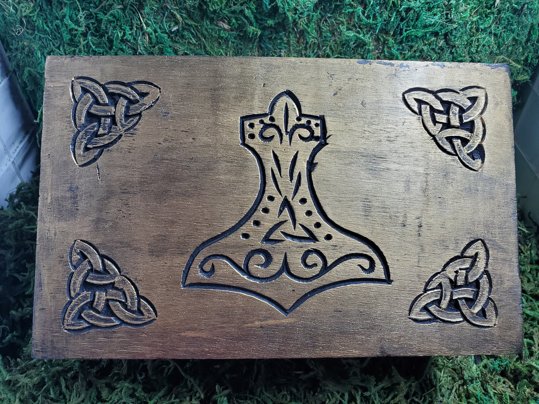 A wooden box decorated with a central Mjolnir, as well as knotwork on each corner.