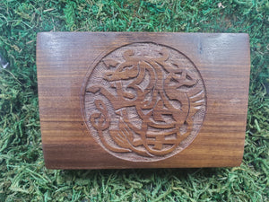 A wooden box featuring the carving of a Pictish knotwork hippocampus--a half horse and half fish creature of Greek and Roman mythology.