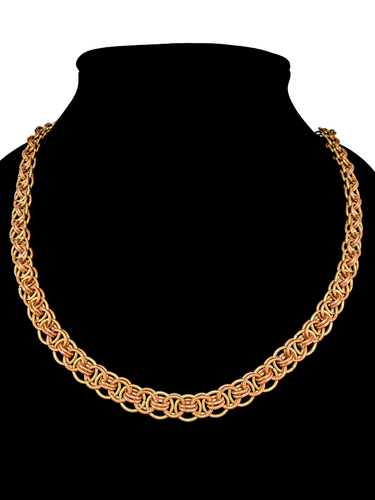 A woven necklace made of interlocking copper and brass colored rings.