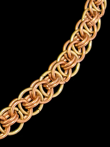 A close-up of the weave pattern of interlocking brass and copper colored rings.