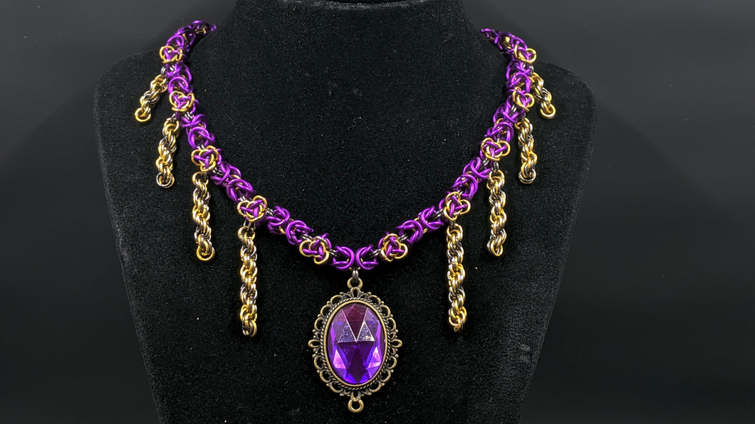 This is a necklace made of chainmail. The necklace is made of royal purple rings, with golden strands made of golden rings coming off the central chain. The very center of the purple chain also has a royal purple pendant set in a brass frame.