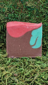 A slice of cold-process soap with primarily brown coloring with red and teal dropswirls.