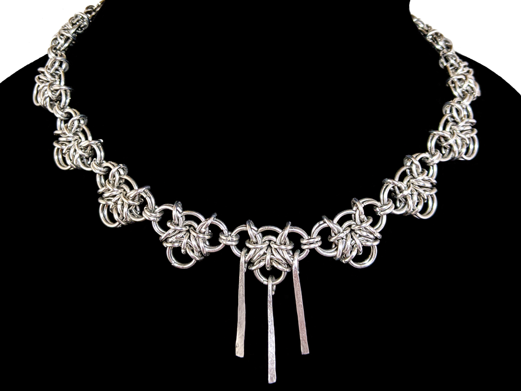 A necklace made of silver links in a woven pattern.