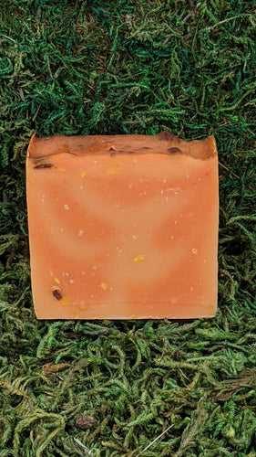 A slice of cold-process soap with a mixture of deep and pale orange with flecks of white and burnt umber.