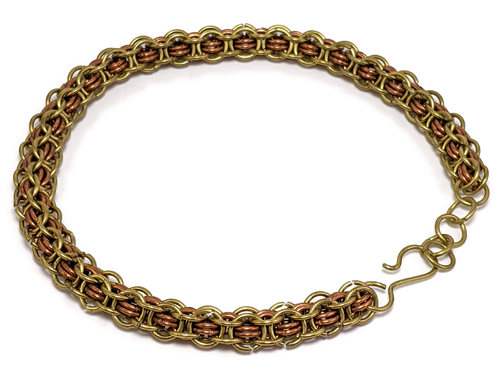 A bracelet made of brass and copper colored rings woven into a chainmail rope.