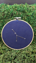 Load image into Gallery viewer, Embroidery of the zodiac constellation Cancer on navy blue fabric in an embroidery hoop.